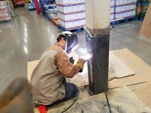 structural welding technician repairing a structural beam