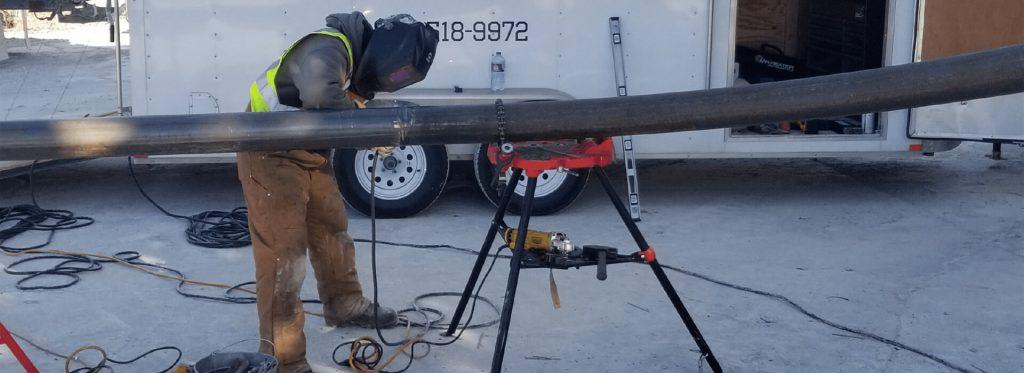 technician welding a large black pipe