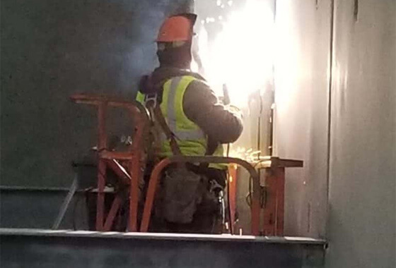 technician welding on a wall