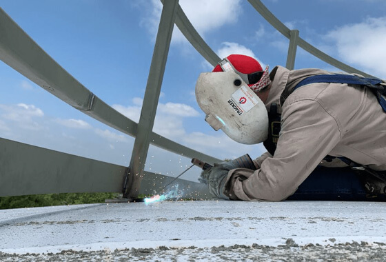 technician welding a handrail on top of a water tower