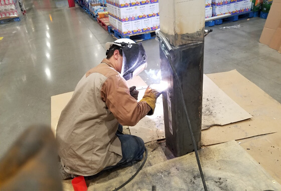 technician welding on a structural beam