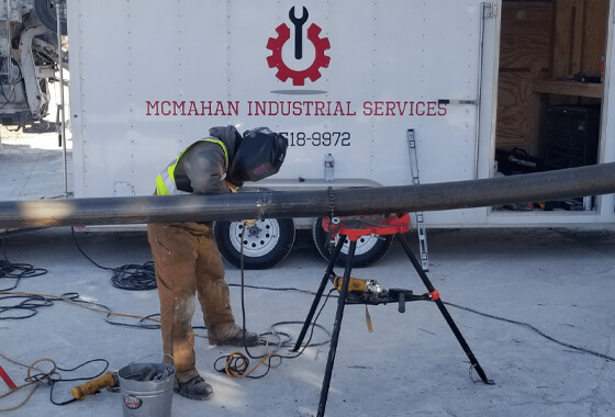 technician welding a large black pipe on a tripod