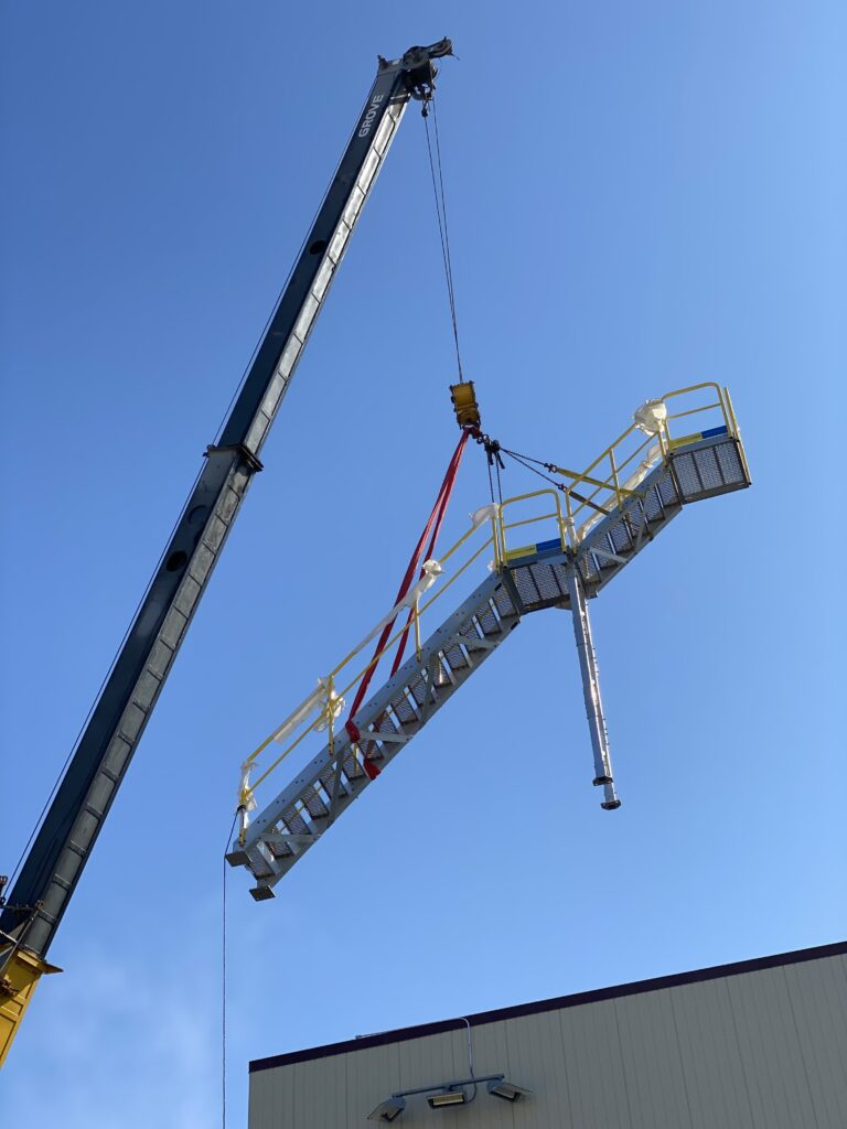 structural welding team uses crane to move staircase